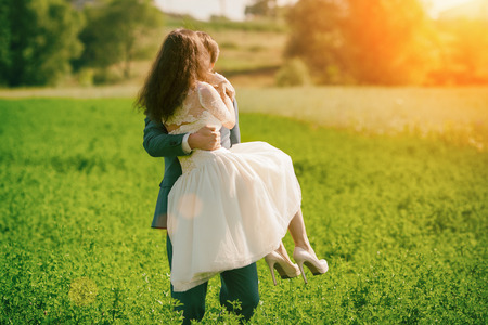Happy kissing wedding couple outdoors on the meadow. Man is holding woman in his arms Stock Photo