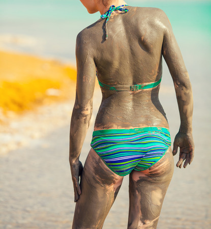 spa mud: Spa procedure. Woman smearing therapeutic mud mask on the body on the beach