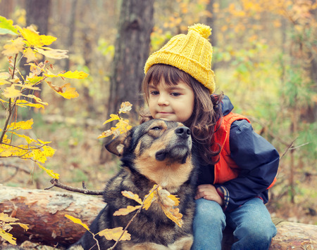 sad cute baby: Sad little girl walking with dog in the fores Stock Photo