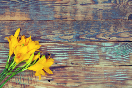 parting: Yellow lily flowers on a wooden background