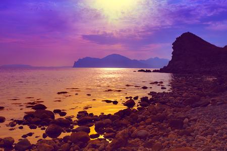 purple sunset: Purple sunset over rocky beach Stock Photo