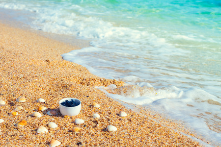 spa mud: Dead sea mud for spa treatments in a cup on the beach