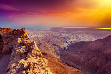 desert sun: Beautiful sunrise over Masada fortress. Ruins of King Herods palace in Judaean Desert. Stock Photo
