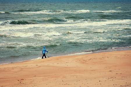 latvia girls: Woman on the beach. Nordic walker on the beach with stormy sea Stock Photo