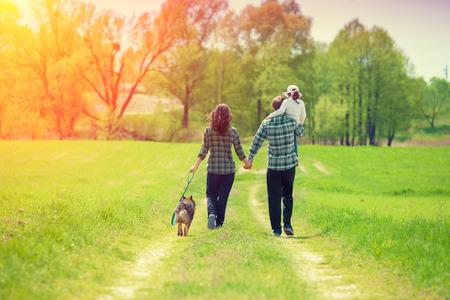 Familia feliz con el perro que recorre en el camino de tierra rural. Niña que se sienta en el hombro del padre