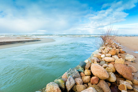 Delta in the daytime. Rocky bank of river. The river flows into the sea Stock Photo
