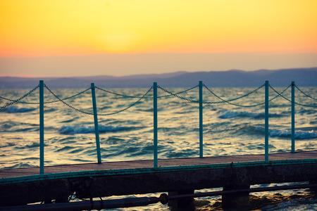 balaton: Wooden bridge over lake Balaton at sunset