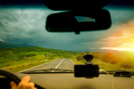 windscreen: View from windscreen. Driving a car in Tuscany valley Valdorcia in stormy weather at sunset, Italy Stock Photo