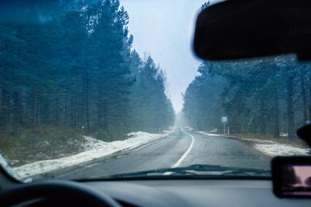 windscreen: View from windscreen. Driving a car on winter road in blizzard