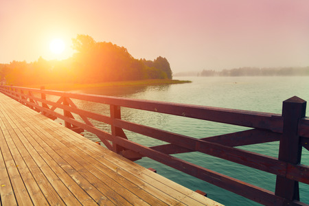 Wooden bridge over lake in early misty morning Stock fotó - 58958166