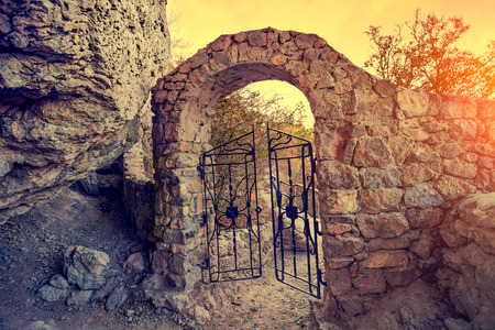 open gate: Open gate in rock at sunset