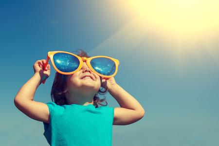 大きなサングラスをかけた太陽を見て幸せな少女 写真素材