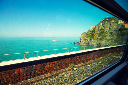 railway transportation: view at ligurian sea, from a window of running train. Cinque Terre, Italy