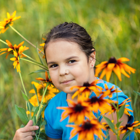 portrait of smiling little girl walking on the flower meadow Stock Photo