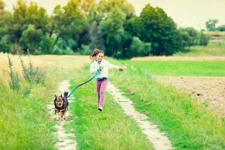 Little girl running with dog in countryside