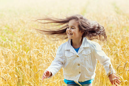 Happy little girl with flying long hair running on the wheat field