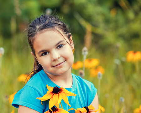 portrait of smiling little girl walking on the flower meadow Stock Photo