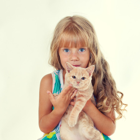 Cute girl hugging a little cat isolated on white background photo