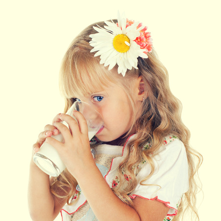 Little girl drinking milk from glass photo