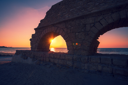 Remains of the ancient Roman aqueduct in ancient city Caesarea at sunset, Israel.
