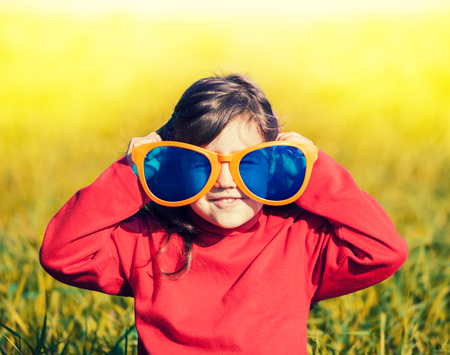 Smiling happy little girl with big sunglasses walking in the meadow in sunny day. Girl holds sunglasses. 版權商用圖片