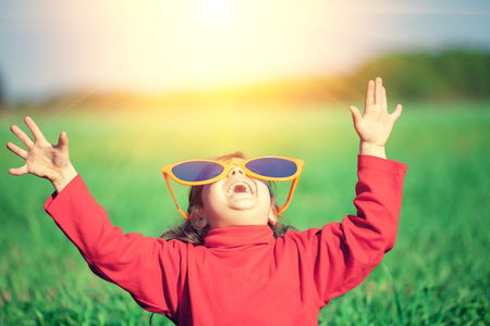 Happy little girl with hands in the air wearing big sunglasses and looking at the sun Stock Photo - 61067098