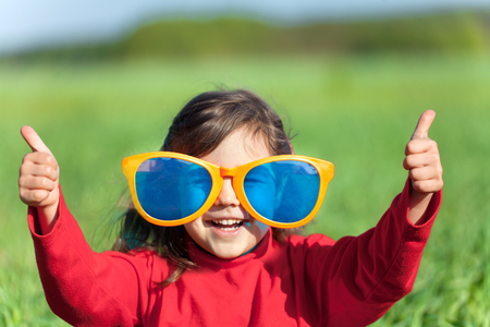 Happy little girl with big sunglasses walking in the meadow and looking at the sun. Girl with hands in the air make thumbs up