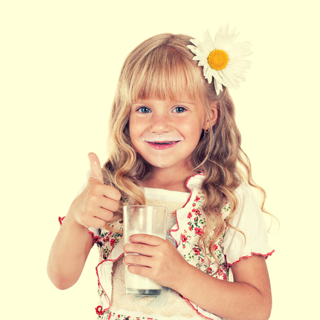 child girl with thumb up drinking milk from glass photo