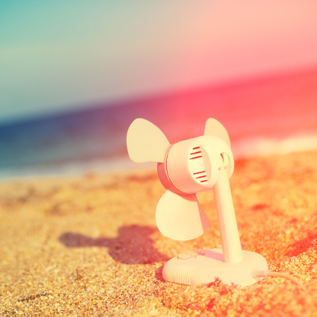 hot day: electric fan blowing on the beach in hot summer