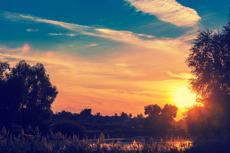 Rural landscape with lake at sunset Stock Photo