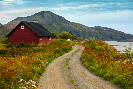 Mountain road along fjord and fishing village. Norway Stock Photo