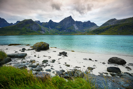 Fjord at sunset in rainy day, Rocky beach in evening, Beach with white sand. Beautiful nature of Norway. Lofoten islands Stock Photo