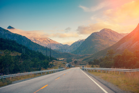 Mountain road at sunset with blue light cloudy sky