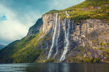 Mountain landscape with cloudy sky. Beautiful nature Norway.Geiranger fjord. Seven Sisters Waterfall