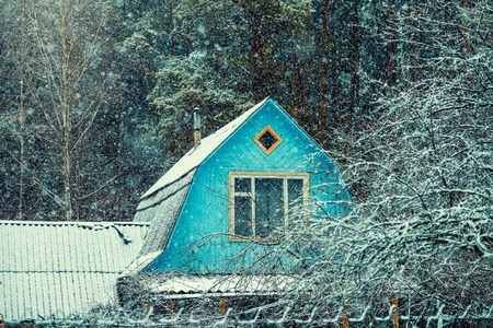 Wooden roof of old hut in the forest in snowfall