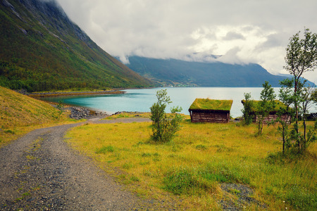 rorbu: Dirt road to fjord. Nature Norway. Beautiful nordic mountain landscape with typical wooden fishermans house (rorbu)