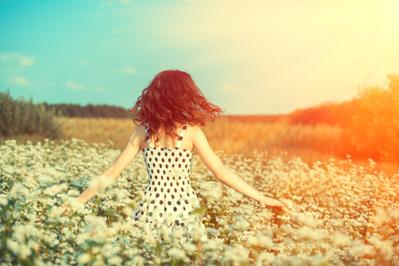 nature of sunlight: Young happy girl walking on the buckwheat field in sunny day