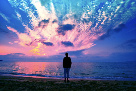 Silhouette of man on the beach looking at magical sunset