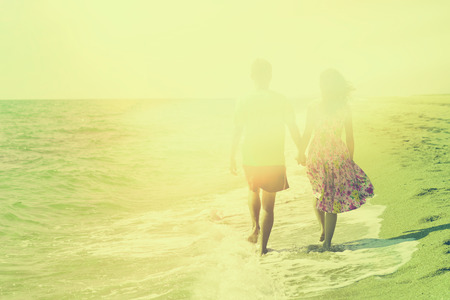 Young couple holding hands and walking carefree on the beach on summer vacation. Retro faded effect color correction