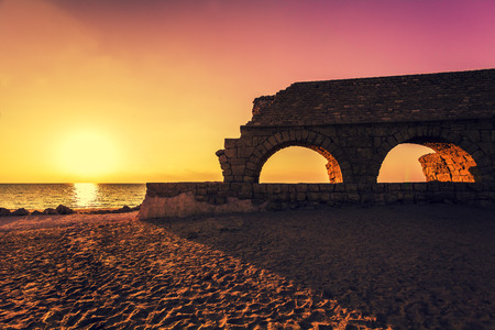 Remains of the ancient Roman aqueduct in ancient city Caesarea at sunset. Israel. Stock Photo
