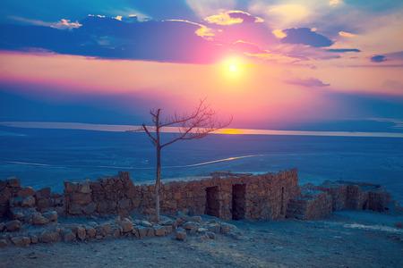Beautiful sunrise over Masada fortress. Ruins of King Herods palace in Judaean Desert. Stock Photo