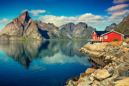 피 요 르 드에 아름 다운 어촌 마입니다. 푸른 하늘, 물, 바위 해변와 낚시 집 (rorby)에서에서 반사와 아름 다운 자연. Lofoten, Reine, 노르웨이 스톡 콘텐츠