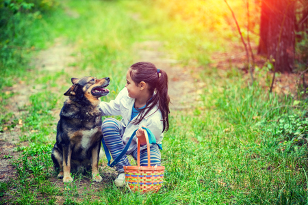 Happy smiling little girl with picnic basket sitting with dog on the grass in the forest. Girl and dog looking to each other Stock Photo