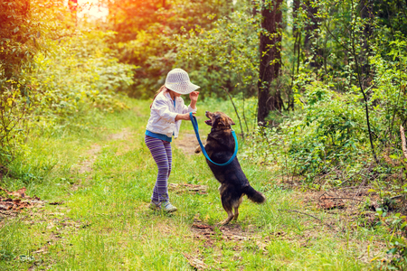 Little girl schooling dog outdoor in a forest