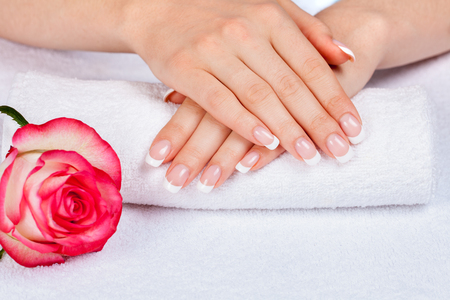 forefinger: Beautiful female hands with french manicure on a white towel near rose flower. Manicure salon