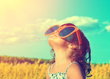 大きなサングラスをかけた夏の麦畑で太陽を見て幸せな少女