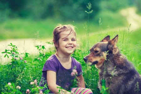 dirt: Happy  little girl with dog on the clover lawn in countryside in summer. Girl and dog sitting back to camera