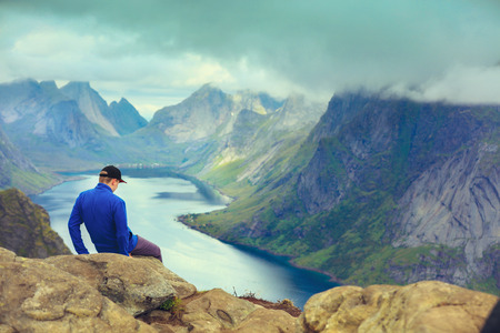 A man sits on the mountains cliff edge. Beautiful mountain landscape. Nature Norway, Lofoten islands Stock Photo