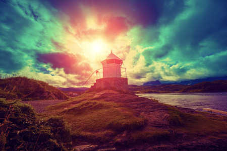 sunup: lighthouse against dramatic cloudy sky during sunset Stock Photo