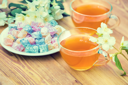 Two cups of green tea with jasmine decorated with turkish delight on wooden table